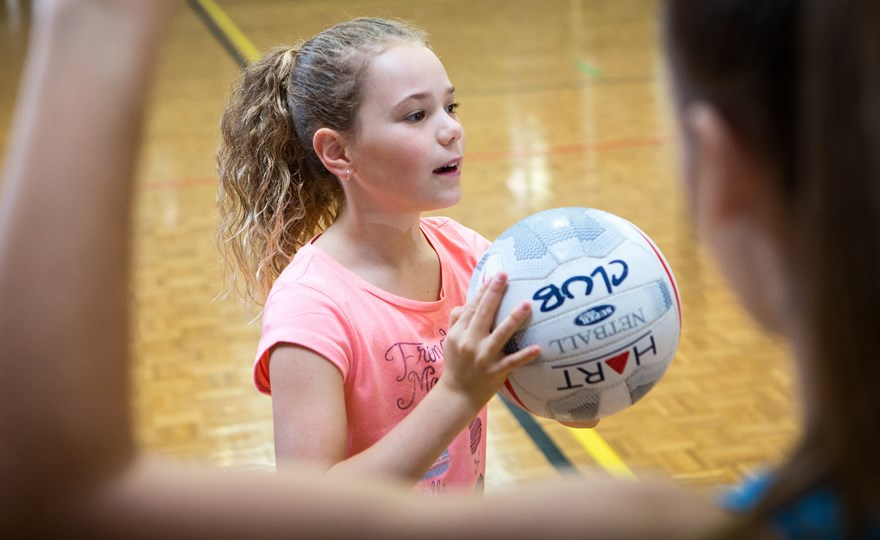 Girl practices netball passing skills at HBF Arena junior netball clinic