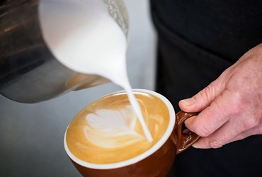 Barista pouring milk into coffee at HBF Arena cafe