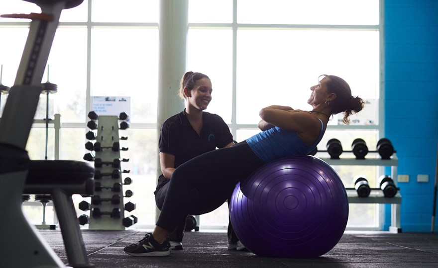 Personal trainer with client on exercise ball HBF Arena